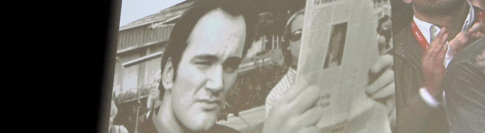 Ein Foto von Quentin Tarantino, das bei einer Preisverleihung auf eine Wand projiziert wird.