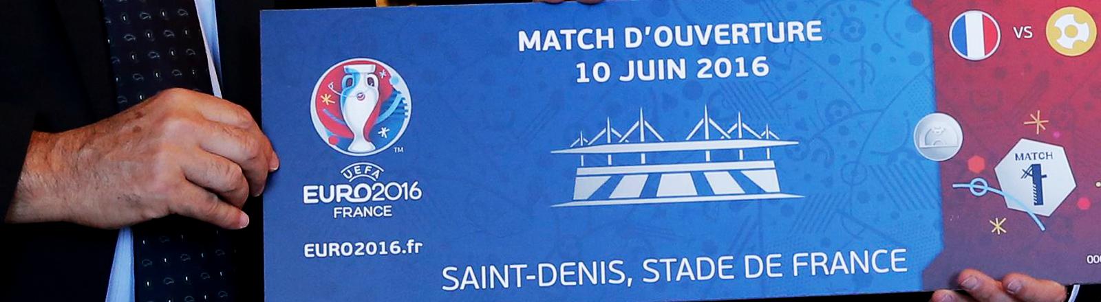 Der französische Präsident Francois Hollande und Michel Platini halten eine überdimensionales Ticket für das Eröffnungsspiel der Europameisterschaft in die Kamera