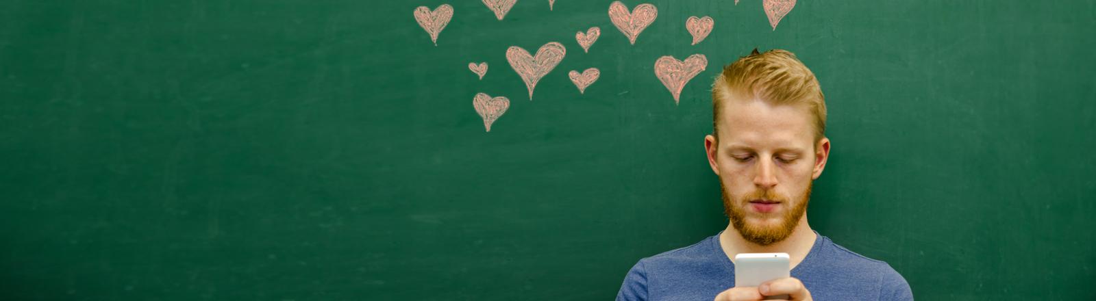 Ein rothaariger junger Mann schaut auf sein Smartphone, im Hintergrund sind Herzen an die Wand gemalt