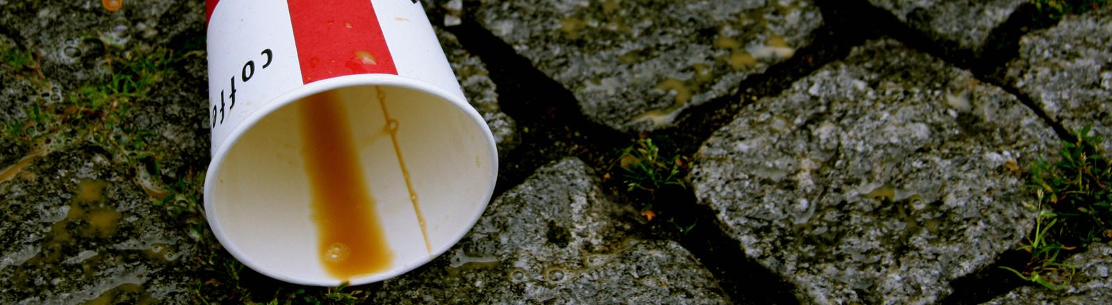 Ein Coffee to go Becher liegt auf Kopfsteinpflaster