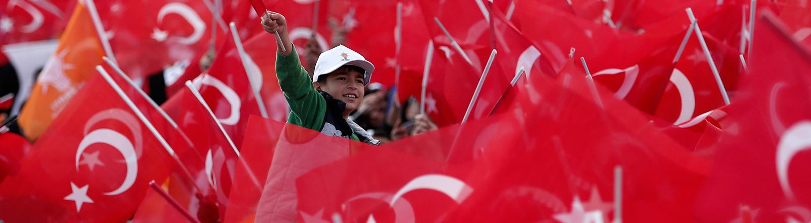 Aus einem Meer aus Türkei-Fahnen lugt ein kleiner Junge hervor und lächelt