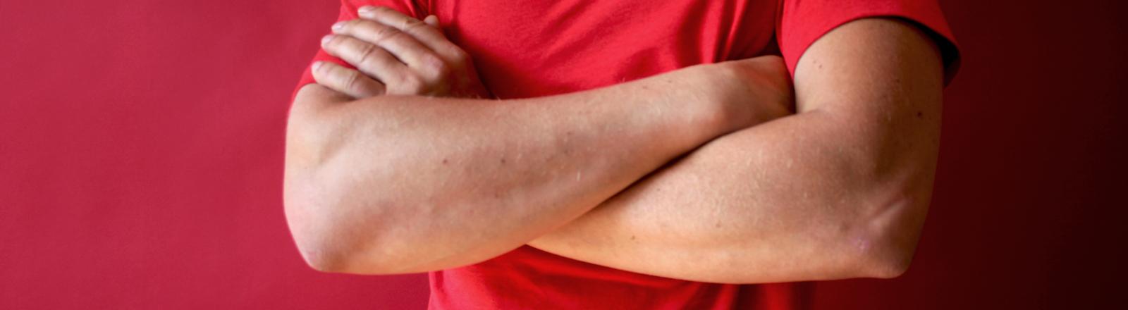 Ein Mann im roten T-Shirt hat die Arme vor der Brust verschränkt
