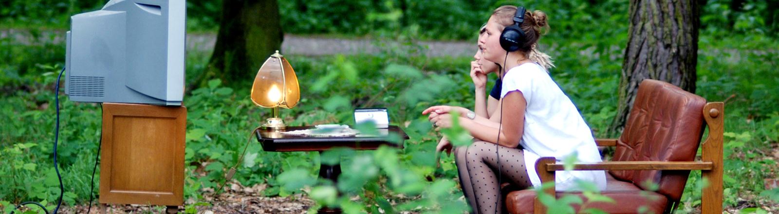 Zwei Frauen gucken TV im Wald