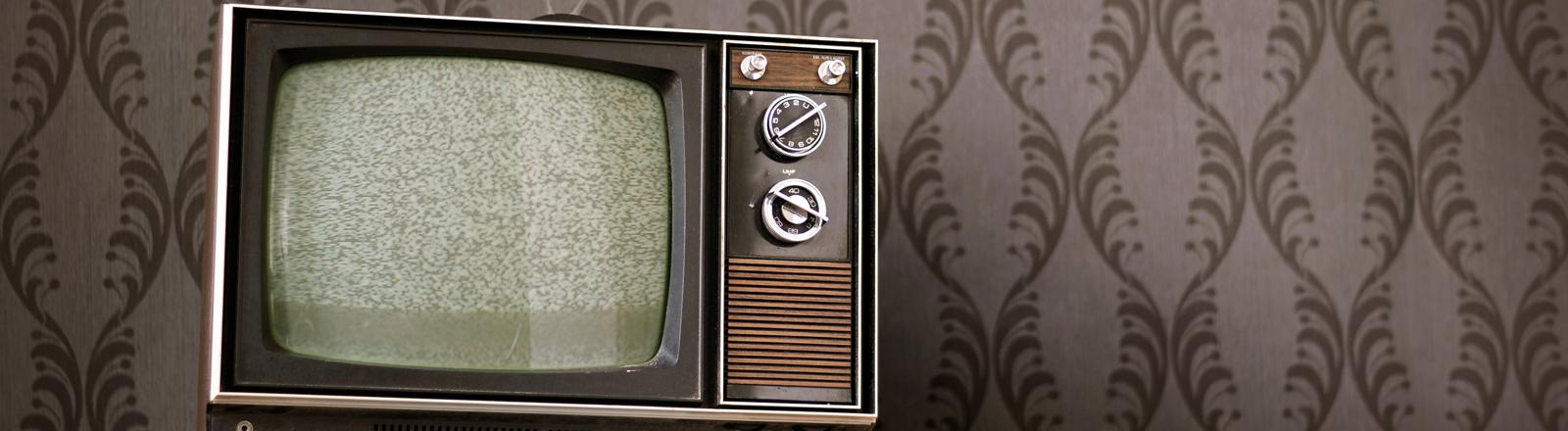 Ein alter Fernseher vor einer 70er Jahre Tapete