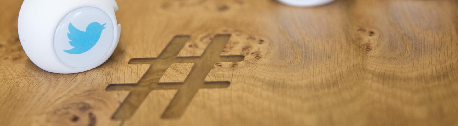 Das Twitterhashtag in einem Tisch, darauf Marketingartikel mit dem Firmenlogo