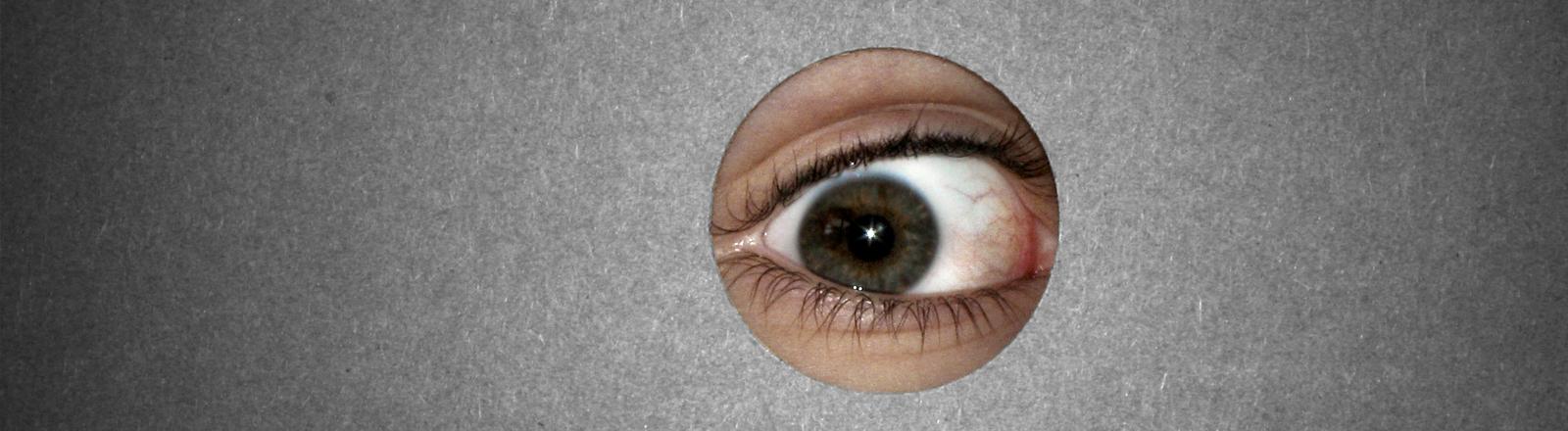 Durch ein Loch in einer Wand ist ein Auge sichtbar, das spioniert