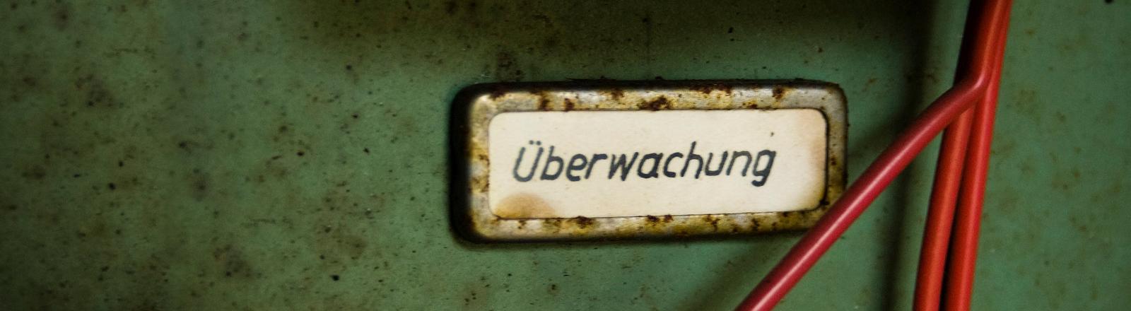 Auf einem Schild an einem Rollcontainer steht Überwachung
