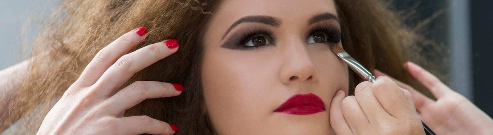 Eine junge Frau wird geschminkt