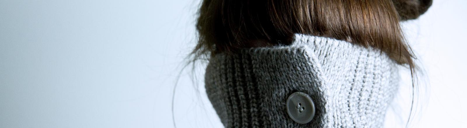 Eine Frau versteckt sich in ihrem Rollkragenpullover