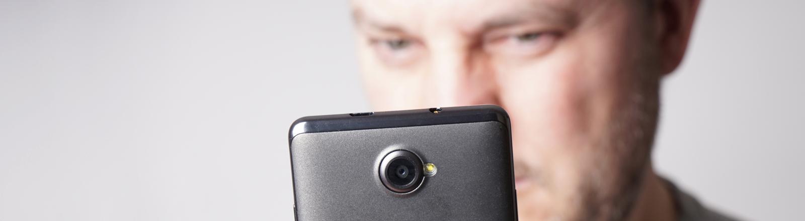 Ein Mann filmt mit einem Smartphone
