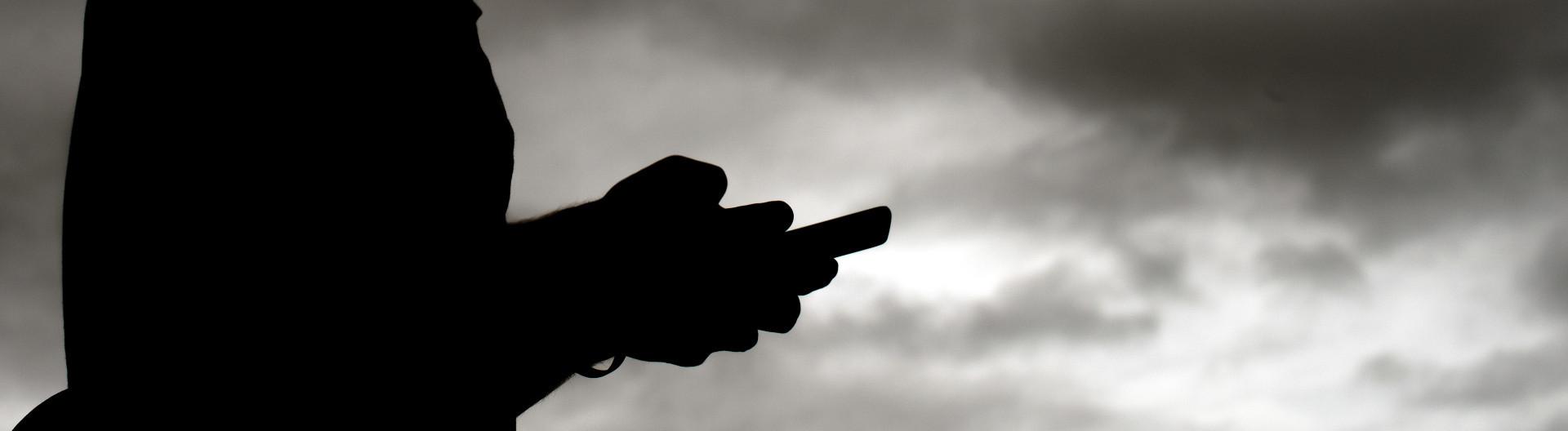 Schattenriss: Mann mit Smartphone vor dunklen Wolken