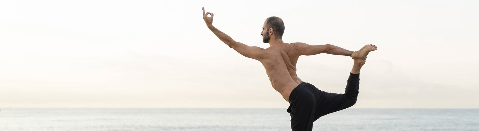 Mann macht Yoga am Strand