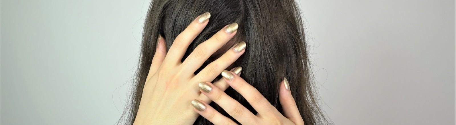 Eine junge Frau verdeckt mit ihren Händen ihr Gesicht.