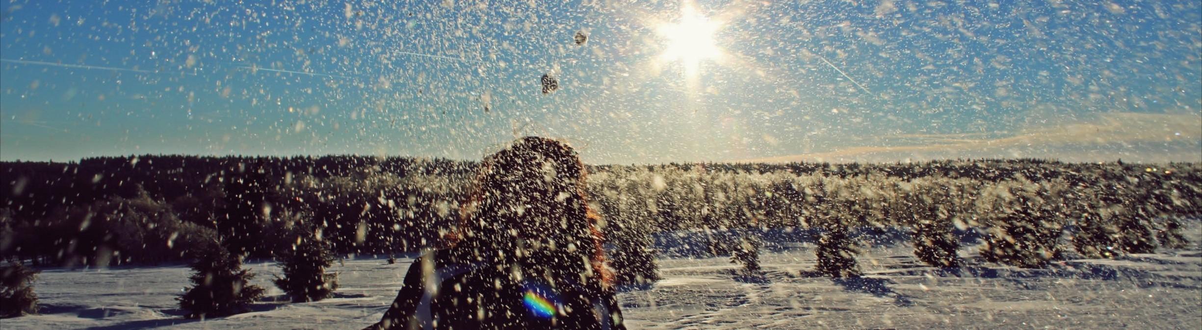 Junge Frau wirft mit Schnee.