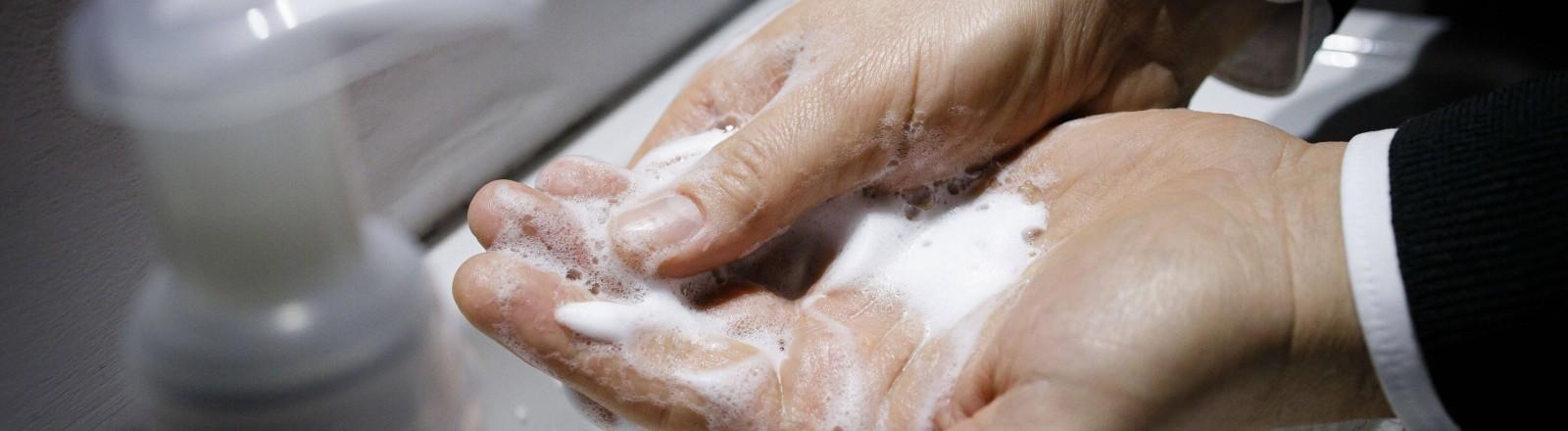 Hände werden im Waschbecken eingeseift