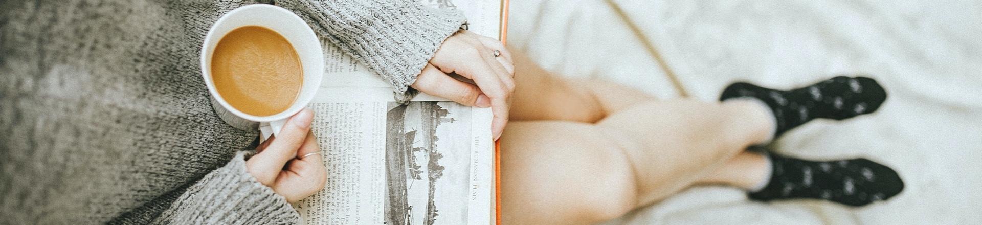 Frau mit Kaffeetasse liest ein Buch