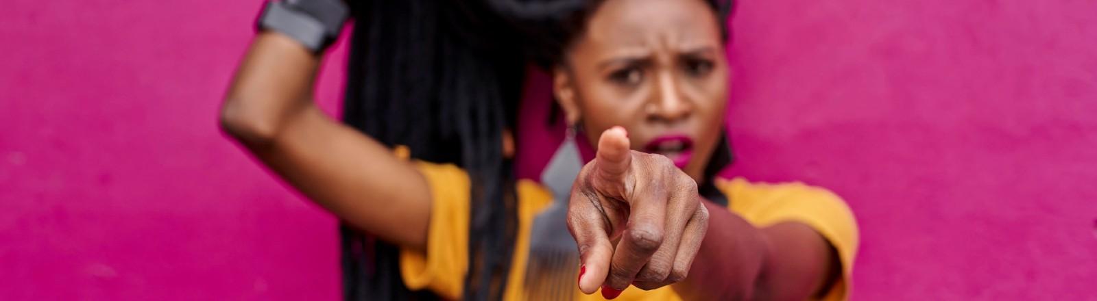 Eine junge Frau zeigt mit dem Finger verurteilend in Richtung des Bildschirms.