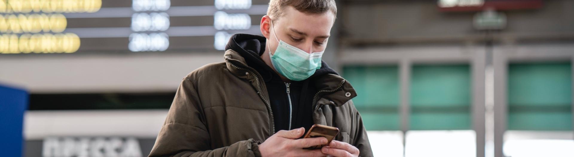 Mann mit Mundschutz schaut auf sein Smartphone