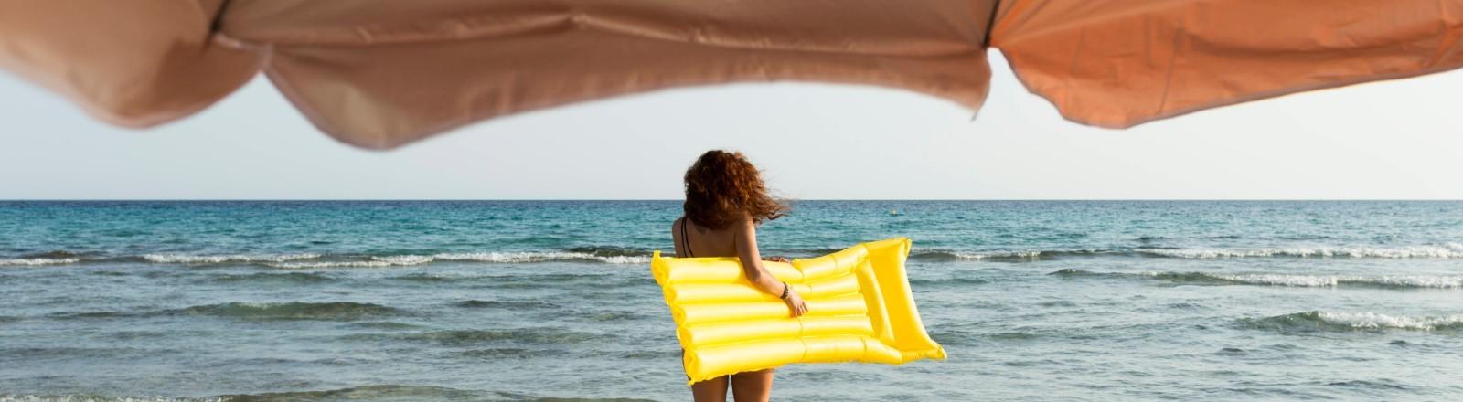 Junge Frau Luftmatratze am Meer.