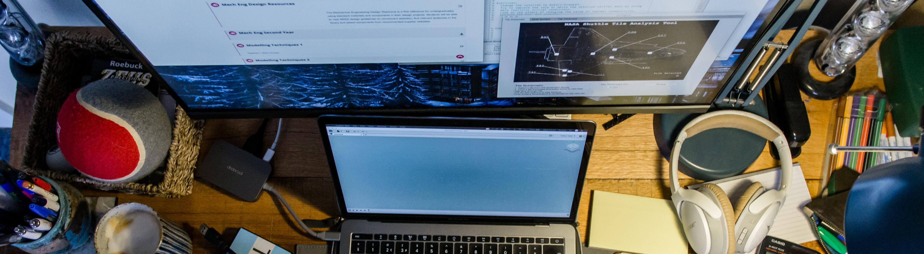Schreibtisch mit Laptop, Taschenrechner, Bildschirm, Kopfhörern und Schreibutensilien