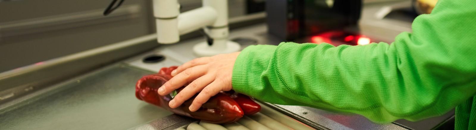 Eine Hand an der Kasse umfasst eine Paprika