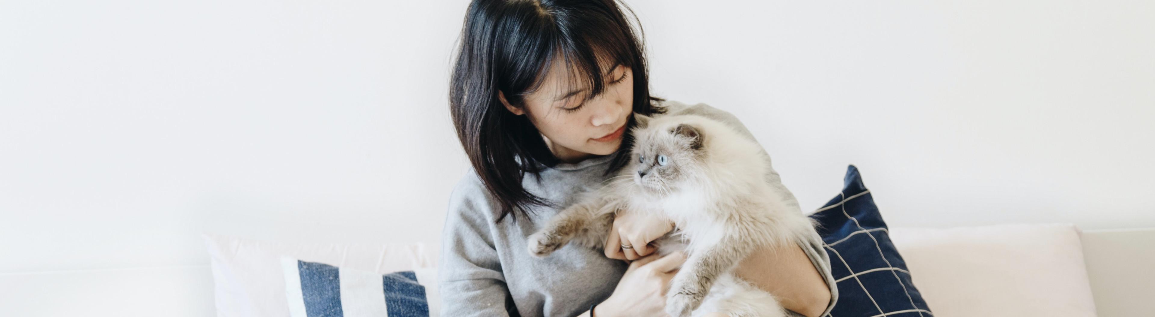 Frau sitzt auf ihrem Bett und Kuschelt mit einer Katze