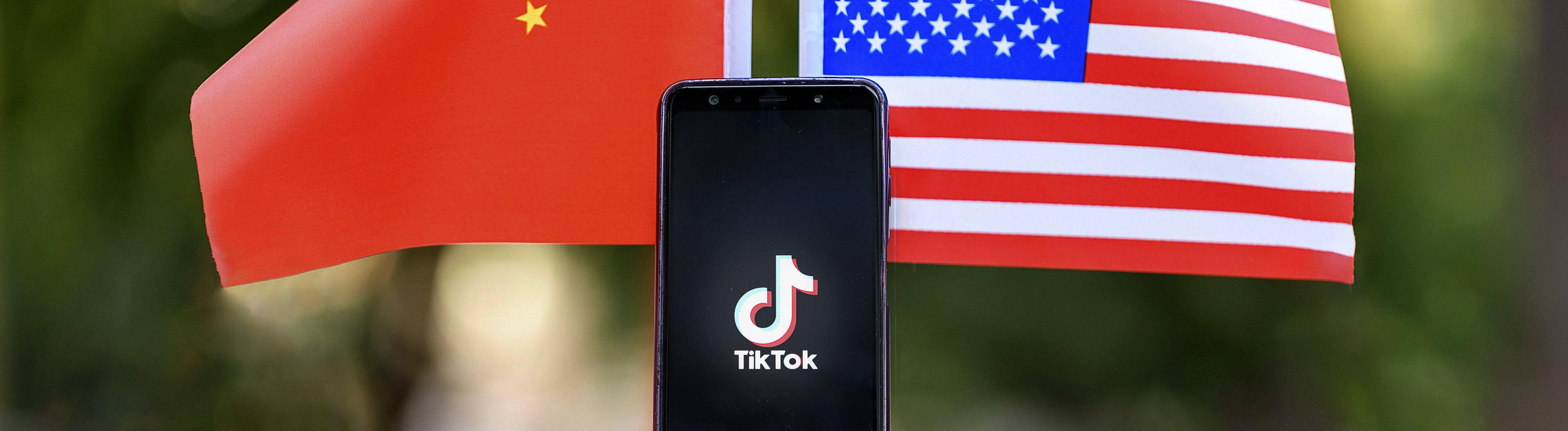 Ein Smartphone, dass das TikTok-Logo zeigt, steht zwischen zwei Miniaturflaggen der Volksrepublik China und der Vereinigten Staaten von Amerika.