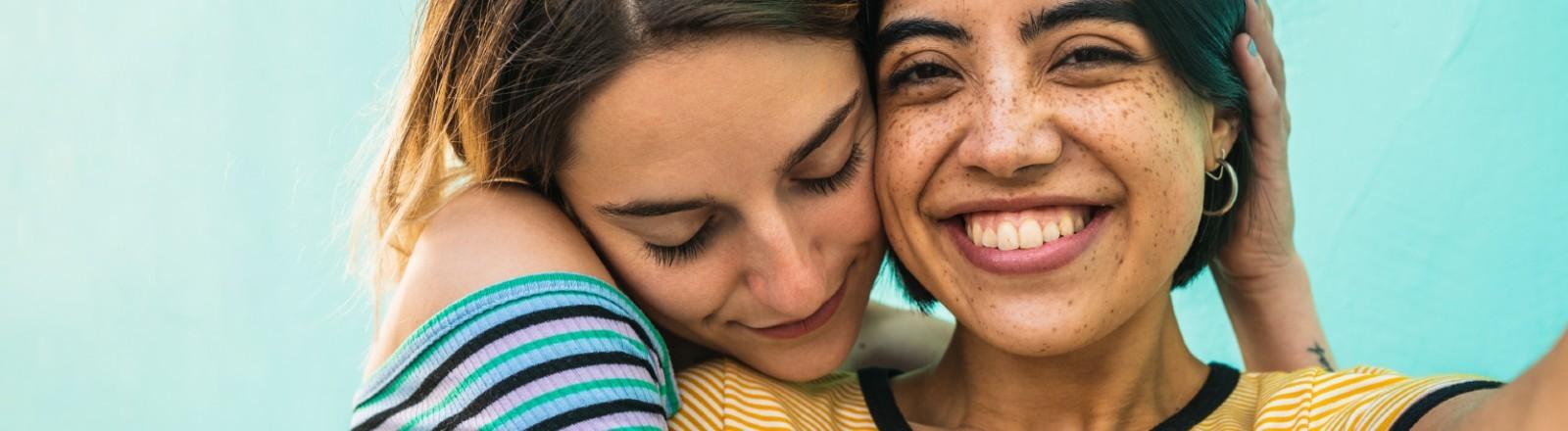 Zwei junge Frauen kuscheln miteinander.