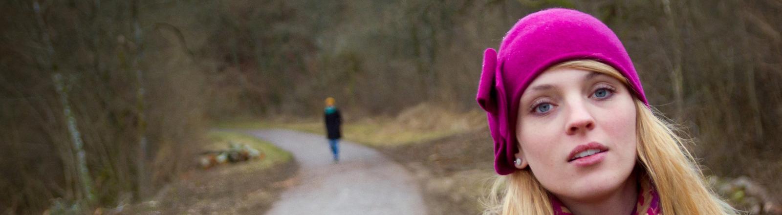 Eine Frau im Wald bei einem Spaziergang. Hinten ist ein mann zu sehen.