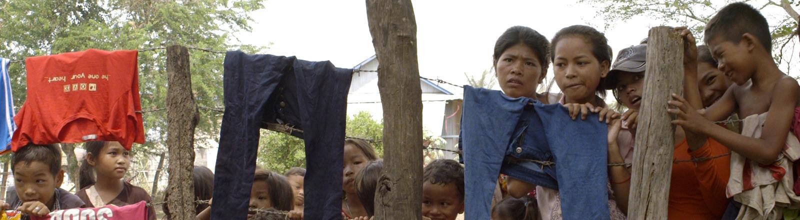 Kinder hinter einem Zaun, an dem Kleidungsstücke hängen.