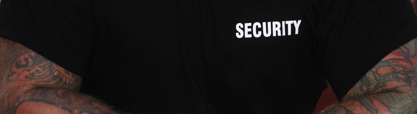 Ein Türsteher mit Security-Shirt
