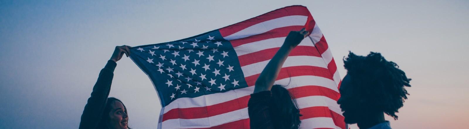 Junge Menschen halten die US-Flagge hoch.