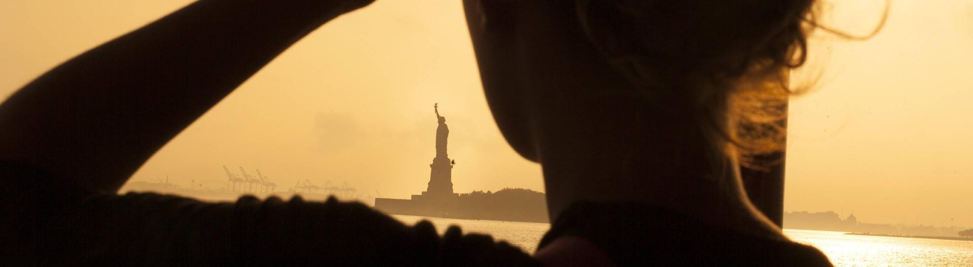 Frau blickt im Sonnenuntergang auf die Freiheitsstatue in New York.