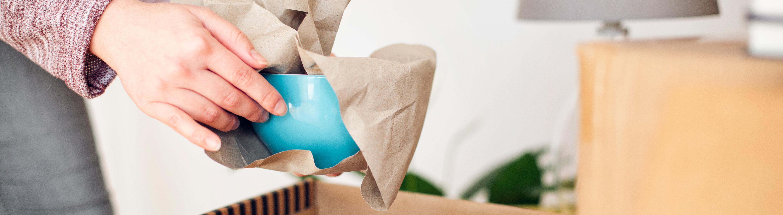Ein Frau packt Geschirr in Papier