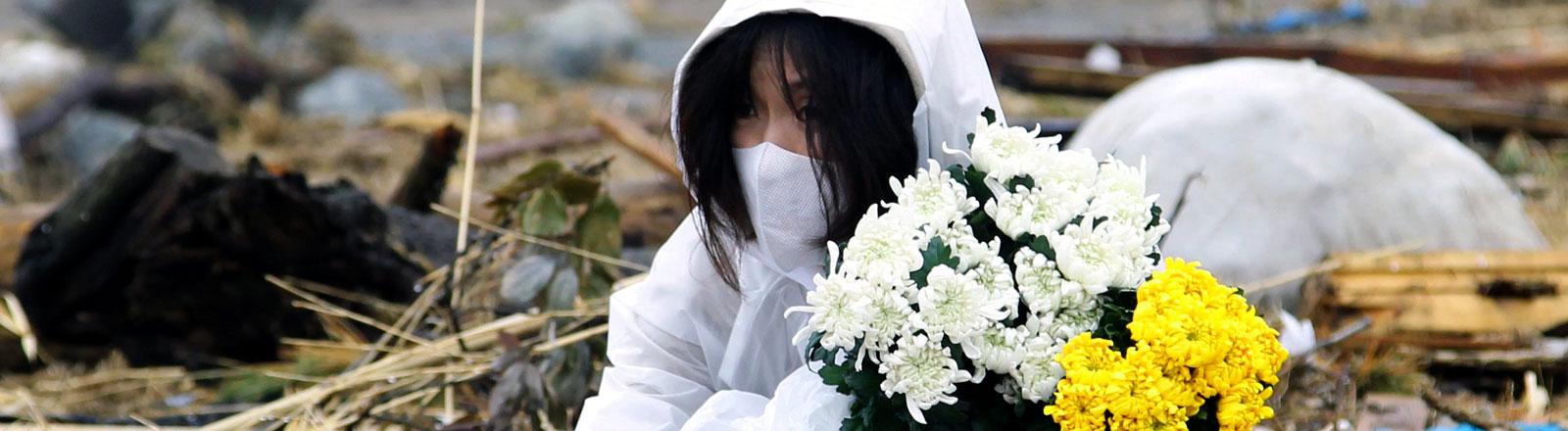 Eine japanische Frau sitzt inmitten von Trümmern mit zwei Blumensträußen und hält Blumen.