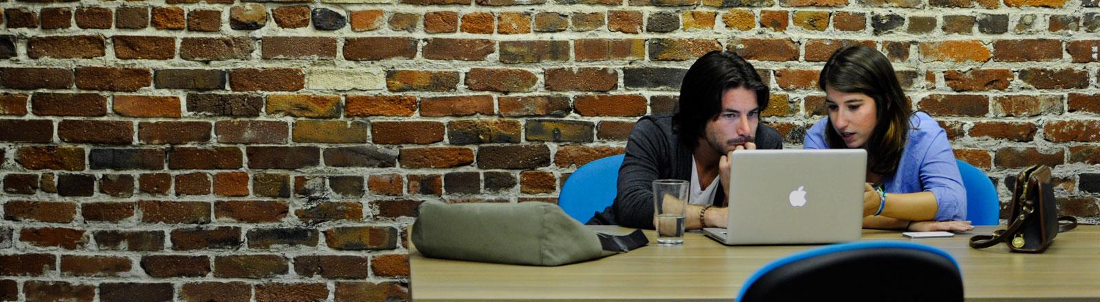 Ein Mann und eine Frau sitzen an einem MacBookPro und arbeiten.