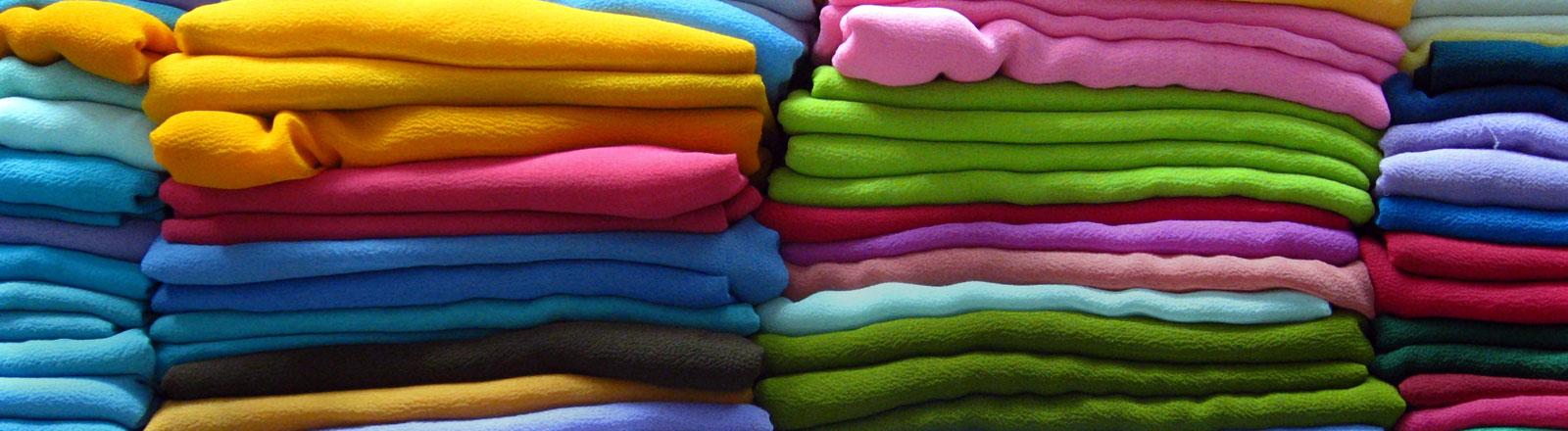 Bunte gefaltete Klamotten liegen in Reih und Glied.