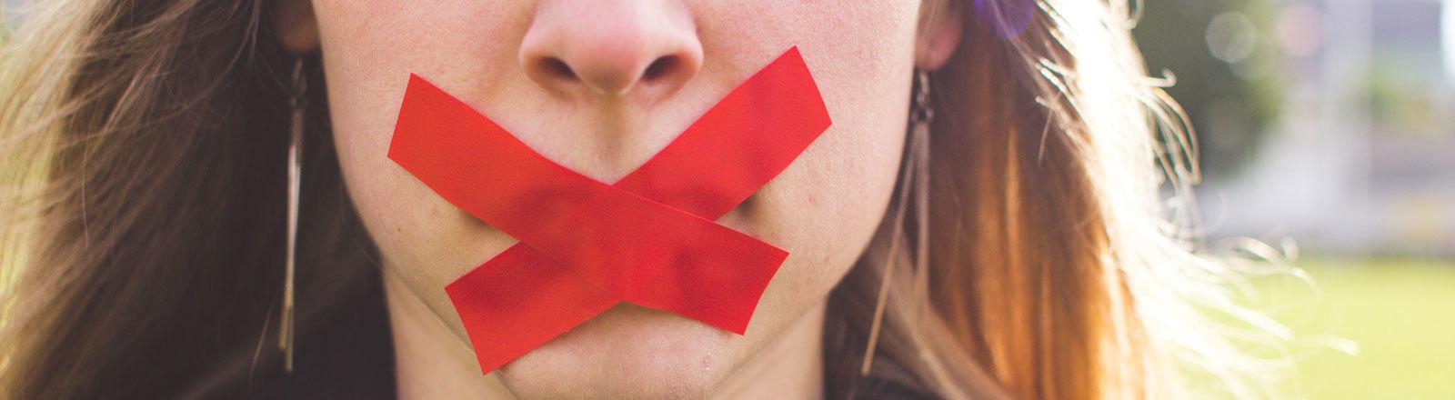 Frau hat vor dem verschlossenen Mund eine rotes Kreuz aus Pflastern.
