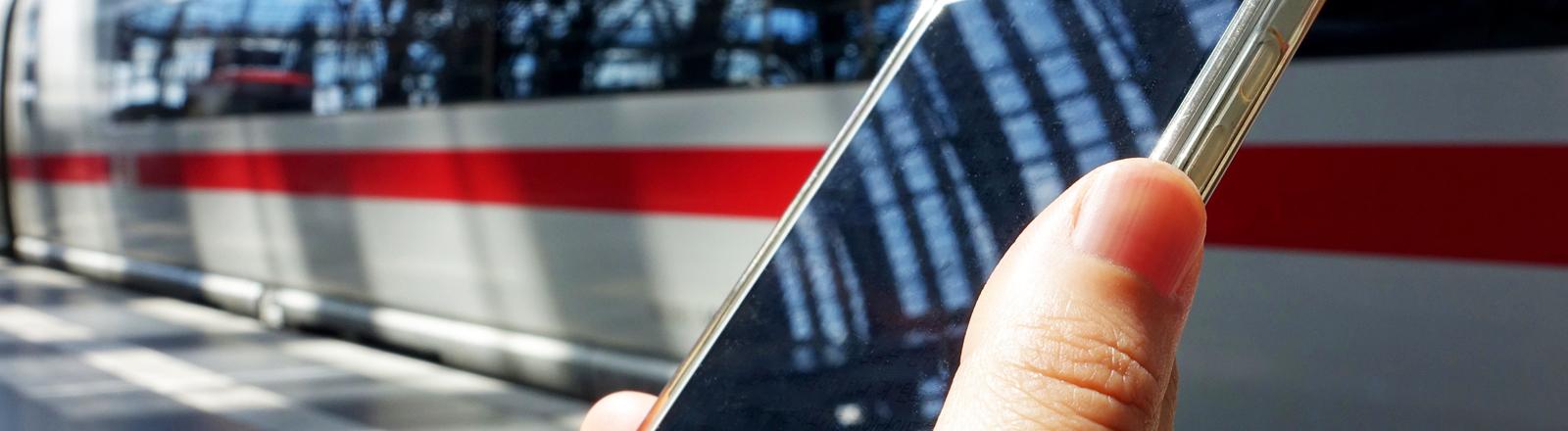 Hand mit Smartphone auf Bahngleis