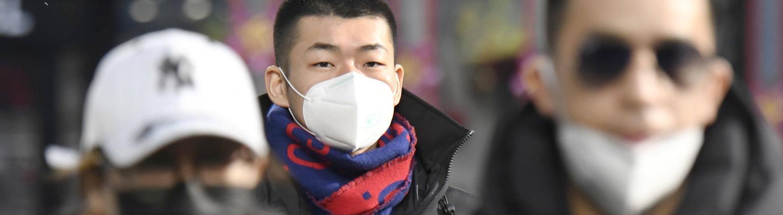 New coronavirus People wear masks in a busy shopping district in Beijing