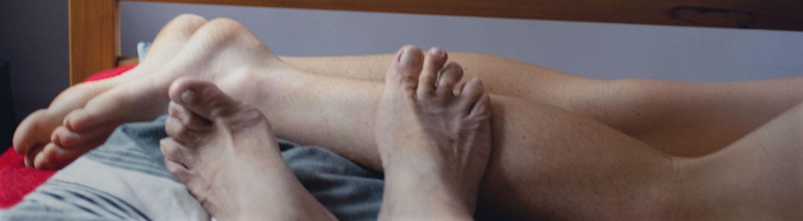 Füße in einem Bett.