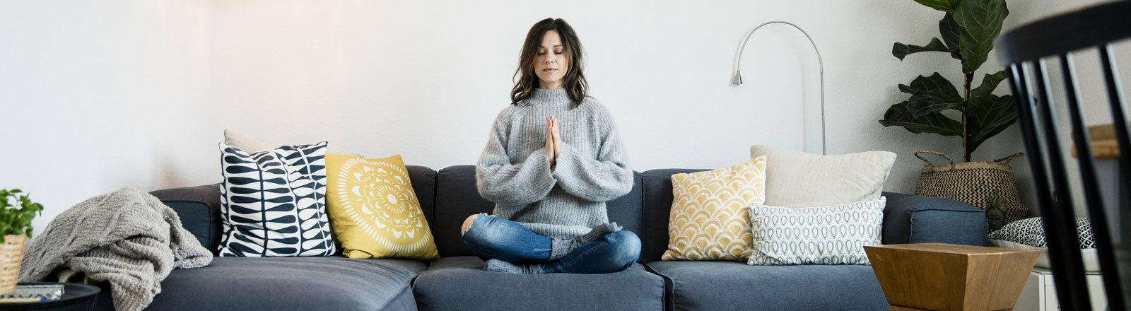 Eine Frau sitzt auf einem Sofa und meditiert.