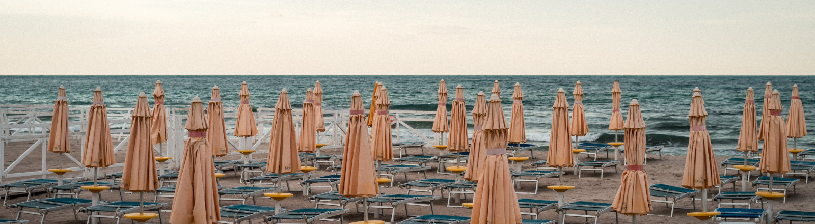 Leere Strandliegen bei Sonnenuntergang