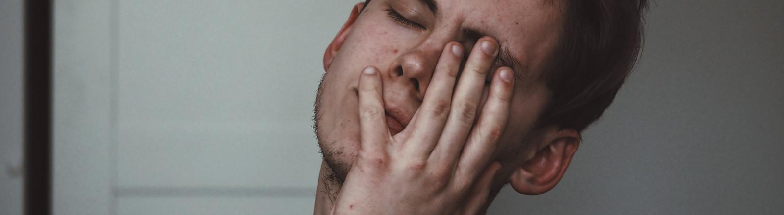 Mann fasst sich enttäuscht mit der flachen Hand ins Gesicht.