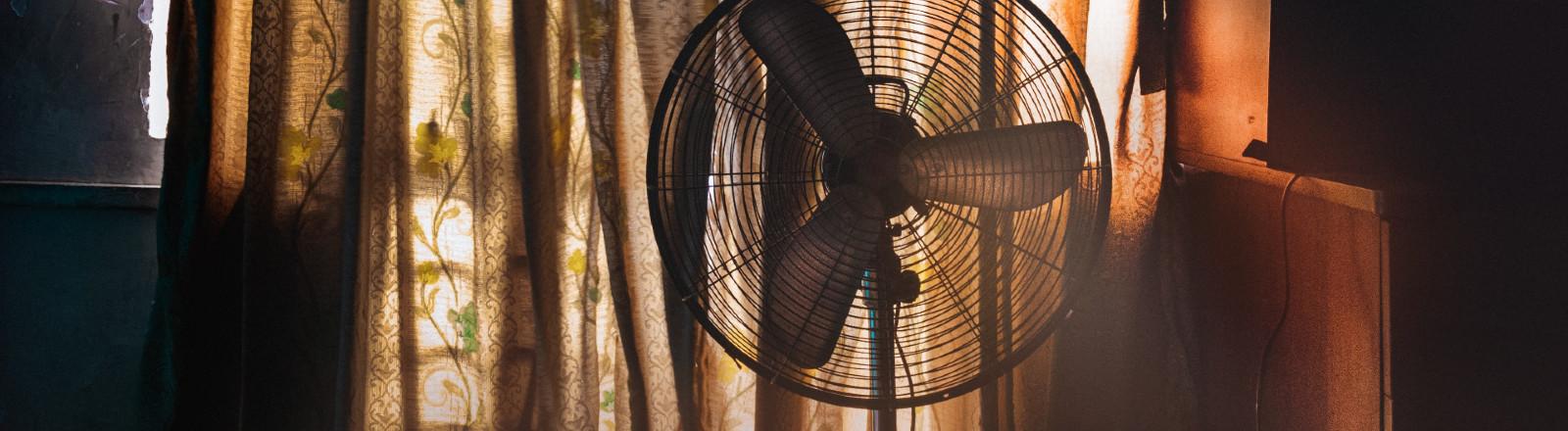 Ventilator steht in einem Raum vor zugezogenen Vorhängen.
