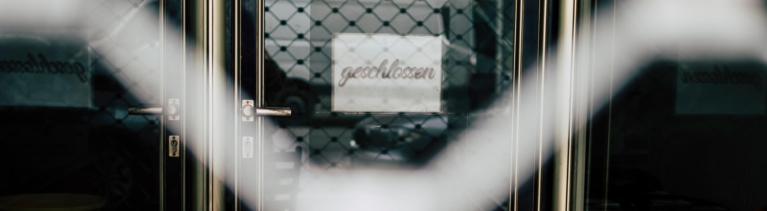 Ein geschlossenes Geschäft durch einen Zaun betrachtet.