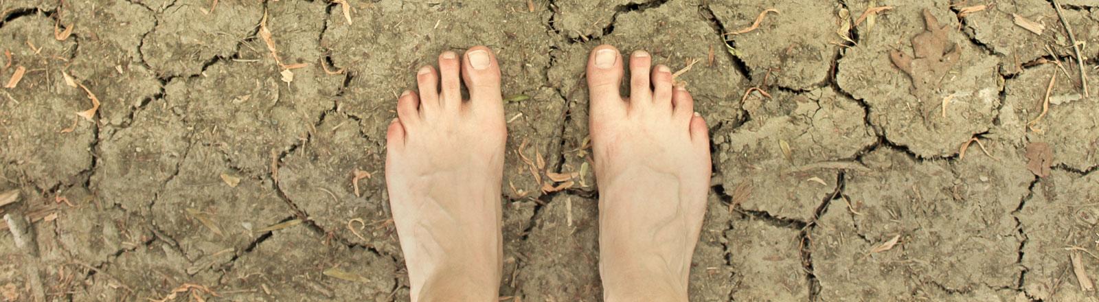 Zwei nackte Füße auf verdorrtem Boden