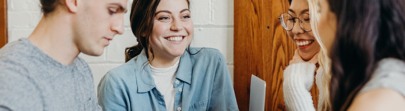 Junge Menschen stehen an einem Tisch und lachen freundlich