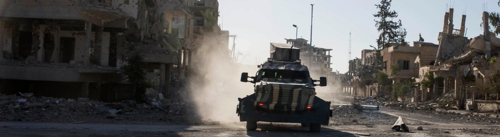 Ein Militärfahrzeug fährt vorbei an Ruinen durch die zerstörte Stadt Rakka in Syrien.