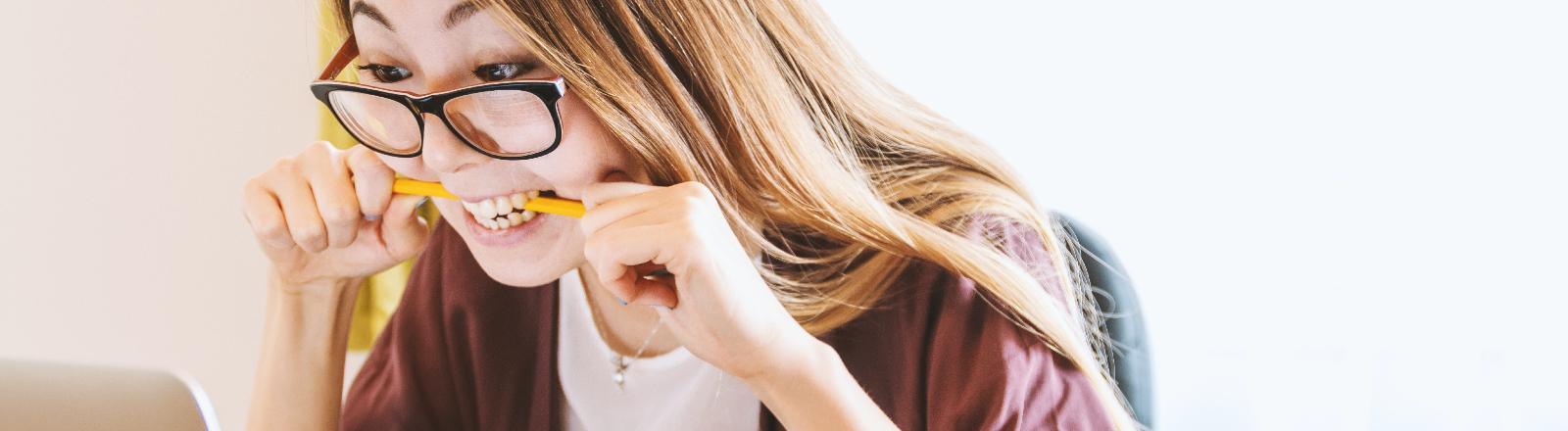 Eine junge Frau beißt auf einen Stift.